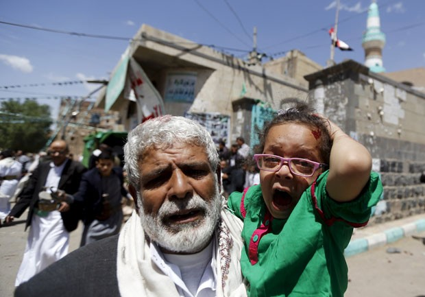Criança ferida é retirada de mesquita atacada por homem-bomba nesta sexta-feira (20) em Sanaa, no Iêmen (Foto: Khaled Abdullah/Reuters)