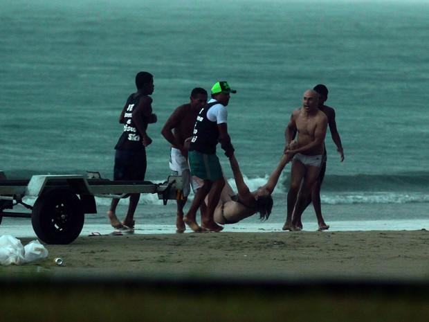 Banhistas socorrem a vítima na praia da Enseada, em Guarujá (Foto: Rogério Soares / Jornal A Tribuna)