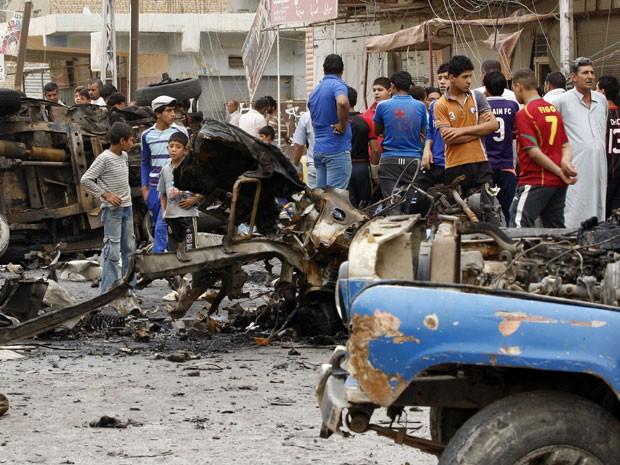 Civis observam carro-bomba que explodiu em bairro xiita de Kamaliyah nesta segunda (20) (Foto: Reuters)