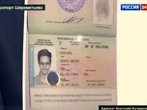 Cópia do documento provisório russo de Edward Snowden é mostrada nesta quinta-feira (1º) por seu advogado, Anatoly Kucherena, em Moscou. O ex-consultor americano recebeu os documentos e deixou a área de trânsito do aeroporto onde estava retido desde 23/6. (Foto: AP/Russia24 via APTN)