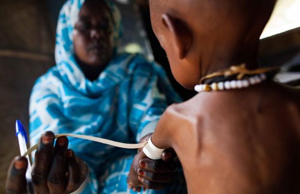 Enfermeira mede braço de criança que sofre de desnutrição, no campo de Abu Shouk, no Sudão, nesta segunda-feira (30) (Foto: AP)