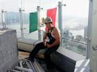 Operário posa com bandeira do México em torre de Trump no Canadá