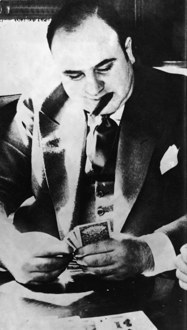 American gangster Al Capone ('Scarface') (1899 - 1947) plays cards in a train compartment during his transport to prison to serve a sentance for tax evasion, October 1931. (Photo by Hulton Archive/Getty Images) (Foto: Getty Images)