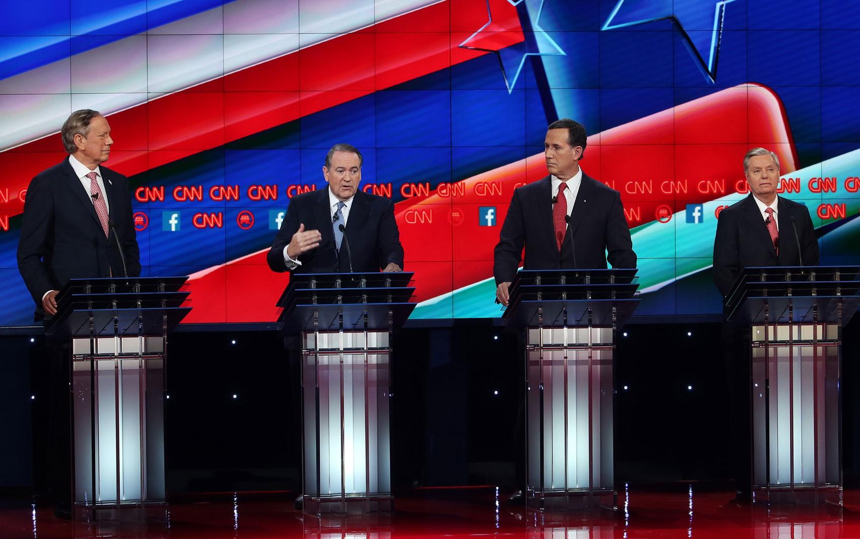 Os pré-candidatos republicanos George Pataki, Mike Huckabee, Rick Santorum e Lindsey Graham participam de debate promovido pela CNN no cassino Venetian, em Las Vegas, na noite de terça (15) (Foto: Justin Sullivan/Getty Images/AFP)