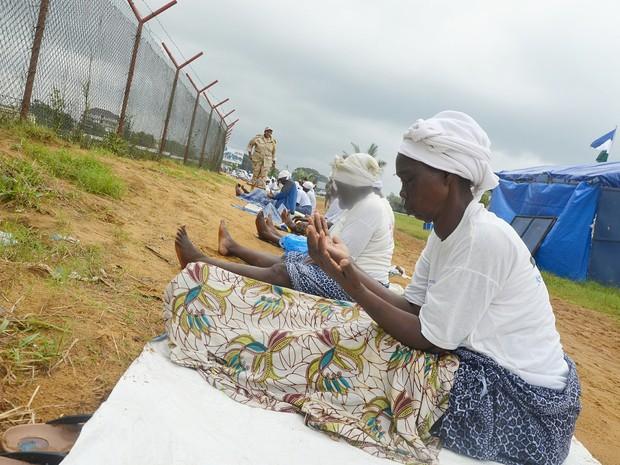 Grupo de mulheres ora para que o ebola deixe a Libéria em área próxima a campo de tratamento da doença em Monrovia (Foto: Zoom Dosso/AFP)
