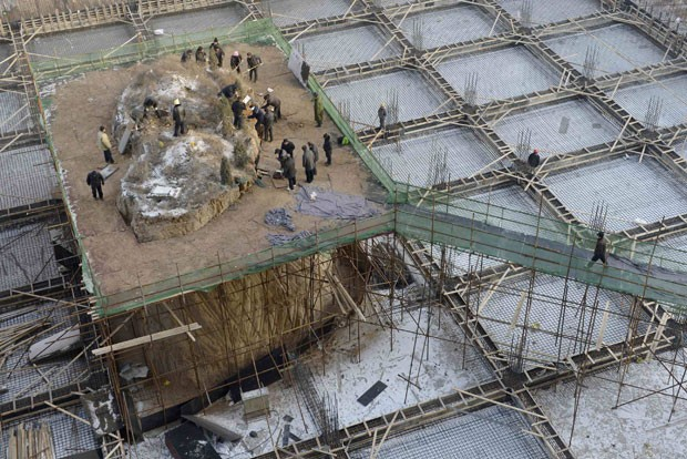 Operários removeram nesta terça-feira (18) um túmulo que ficava no meio de um prédio em construção em Taiyuan (Foto: Reuters)