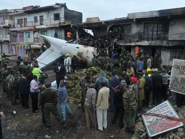 Bombeiros e equipes de resgate trabalham em meio aos destroços de um avião de carga que caiu em um edifício comercial em Nairóbi. (Foto: Tony Karumba / AFP Photo)