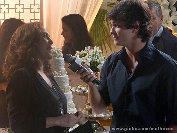 Vera dá entrevista para falar sobre o bolo de casamento que fez, mas Ronaldo vira o assunto (Foto: Malhação / TV Globo)