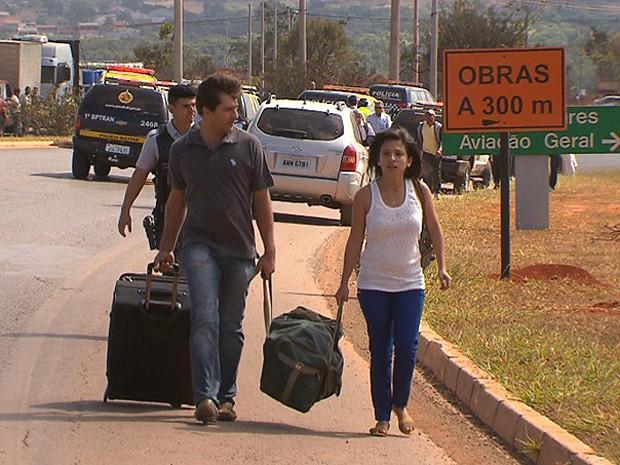 Com via de acesso ao aeroporto JK, em Brasília, bloqueada devido a manifestação de divulgadores da Telexfree, Passageircaminham para chegar aoi Aeroporto JK, em Brasília, passageiros caminham para não perder voo (Foto: TV Globo/Reprodução)