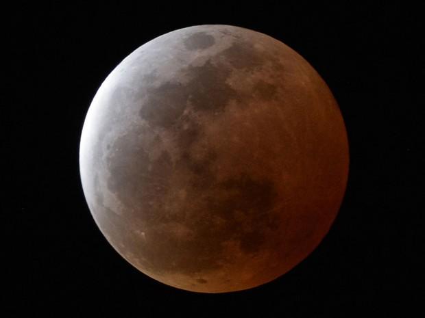 Eclipse lunar total, fenômeno conhecido como 'Lua de sangue', é observado na cidade de Urasoe, em Okinawa, no Japão, neste sábado (4) (Foto: AP Photo/Kyodo News)