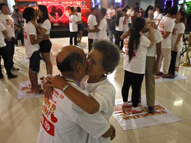 Bunjed Yomjinda, de 74 anos, beija Suwanna Yomjinda, de 72, e outros casais, em tentativa de quebrar o recorde de beijo mais longo, em Pattaya,150 km a leste de Bangkok, Tailândia, nesta terça-feira (12). (Foto: Reuters/Chaiwat Subprasom)