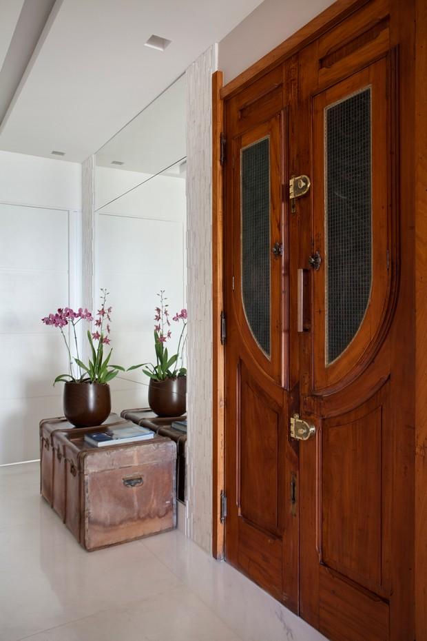 REAPROVEITAMENTO | Alguns móveis e objetos de decoração foram reaproveitados durante a obra. É o caso do baú antigo e da porta. Esta última foi trazida da fazenda da família da moradora (Foto: Denilson Machado - MCA Estúdio/Divulgação)