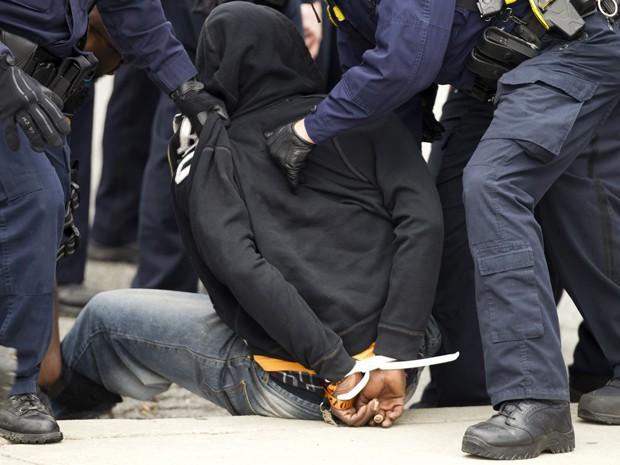 Policiais detém um manifestante durante confronto em protesto pela morte de Freddie Gray, em Baltimore, na segunda (27) (Foto: AP Photo/Jose Luis Magana)