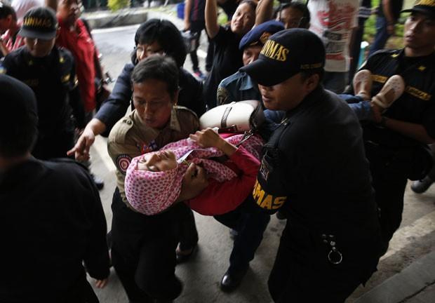 Equipes do governo carregam parente de passageiro do voo da AirAsia que passou mal após saber da localização dos destroços do voo (Foto: Beawiharta/Reuters)