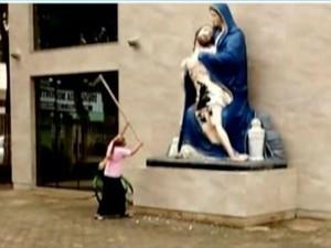Mulher usou uma enxada para danificar a imagem  (Foto: Reprodução Inter TV dos Vales)