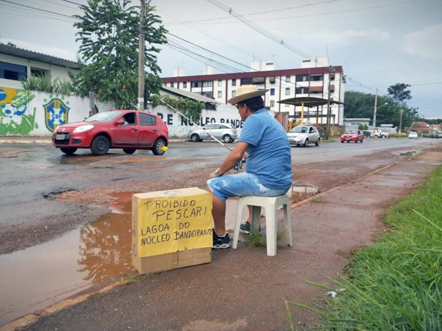 Homem improvisa pescaria em buraco de rua do Núcleo Bandeirante, no DF (Foto: TV Globo/Reprodução)