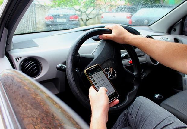 Motorista usa celular enquanto dirige carro ; celular ao volante ; celular no carro ; multa para motoristas que falam ao celular enquanto estão ao volante (Foto: Reprodução/Facebook)