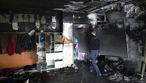 Trabalhador remove quadro de escola incendiada  (Foto: Reuters)