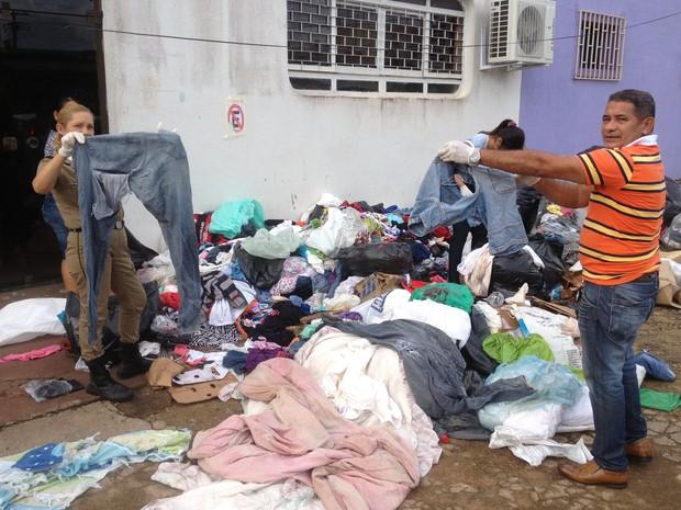 Voluntários mostram roupas rasgastas, já descartadas, embaladas como lixo, e extraviadas por moradores durante a madrugada (Foto: Assem Neto/G1 RO)