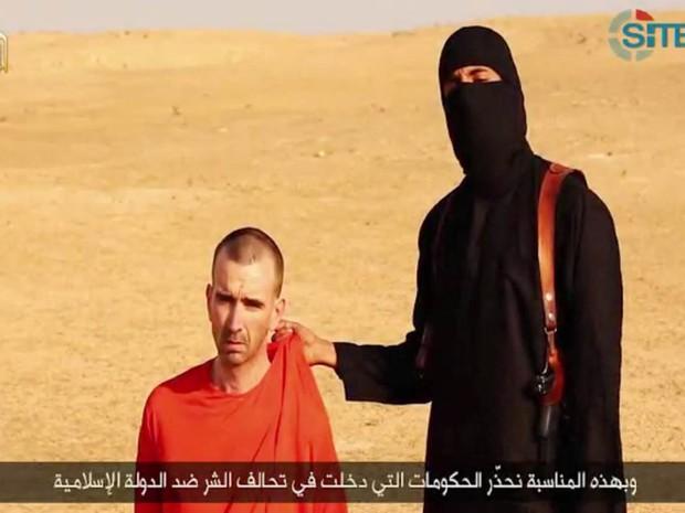 Terrorista do Estado Islâmico faz ameaça dizendo que o homem ao seu lado, identificado como o britânico David Cawthorne Haines, pode ser o próximo a ser decapitado em represália à intervenção militar dos EUA no Iraque (Foto: AFP/SITE Inteligence Group)