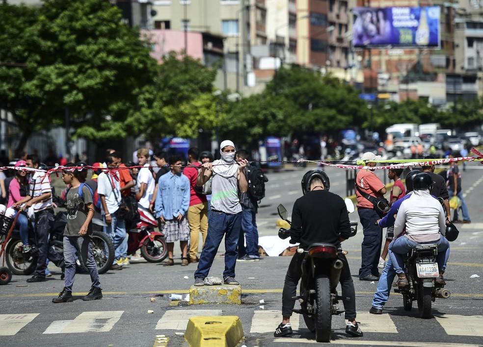 Opositores ao governo de Nicolás Maduro bloqueiam ruas de Caracas nesta terça-feira (18) (Foto: RONALDO SCHEMIDT / AFP)