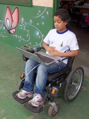 Aluno impulsiona a cadeira de rodas para a frente levantando as sobrancelhas (Foto: Isabella Formiga/G1)