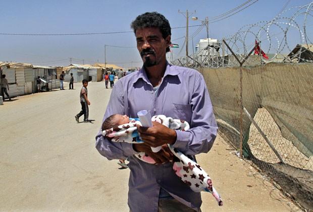 Refugiado sírio segura filha no colo em campo na Jordânia em 24 de julho; Dia dos Pais é comemorado nos dois países no dia 21 de junho (Foto: Raad Adayleh/AP)