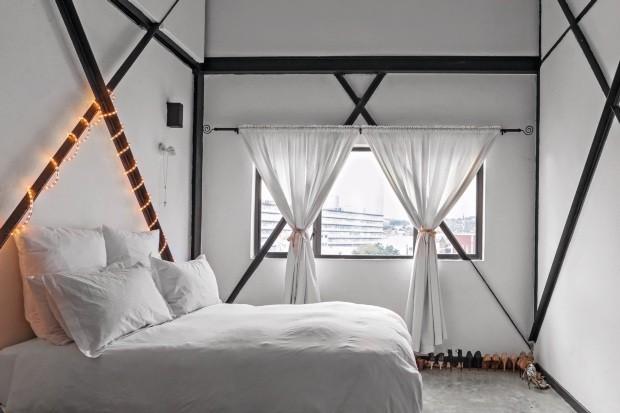 A estrutura original do prédio com as vigas de aço cruzadas no quarto e o telhado aparente foi mantida e valorizada pela moradora (Foto: Lufe Gomes / Editora Globo)