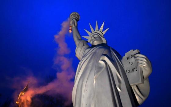 Uma réplica da Estátua da Liberdade emite fumaça em uma arte de protesto criada pelo artista dinamarquês Jens Galschiot. A estátua foi apresentada em Bonn, durante a 23ª Conferência da ONU sobre Mudanças Climáticas (Foto: PATRIK STOLLARZ / AFP)