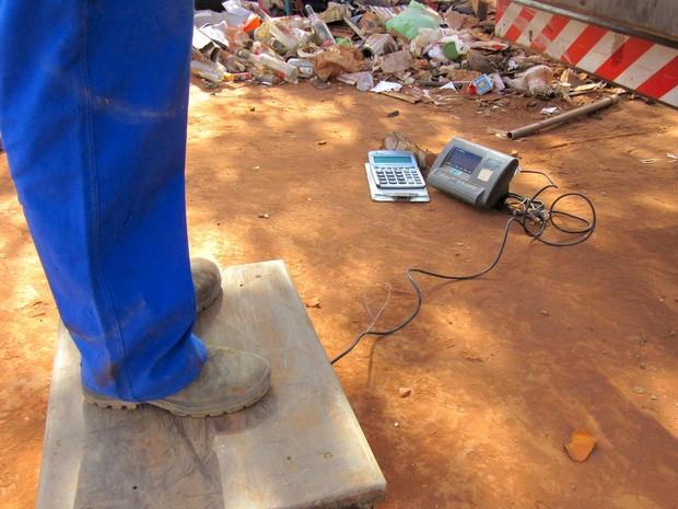 Funcionário de cooperativa calibra balança para pesagem de material reciclável coletado com catadores da Asa Norte (Foto: Alexandre Bastos/G1)