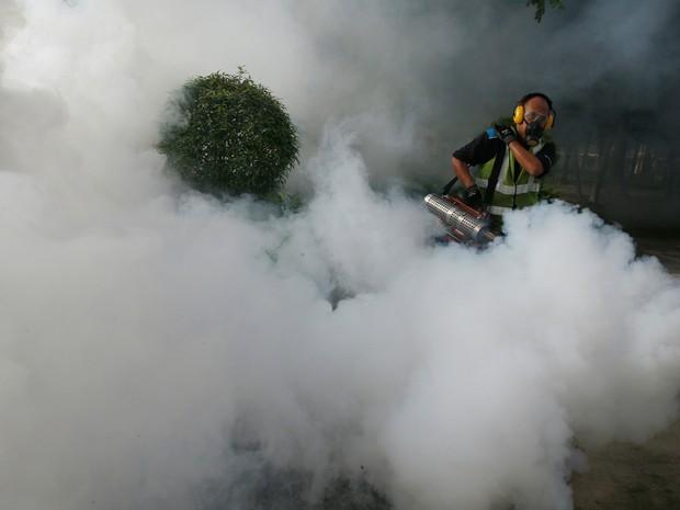 Funcionário passa produto para eliminar mosquitos em uma área onde casos de zika foram descobertos em Cingapura (Foto: Edgar Su/Reuters)