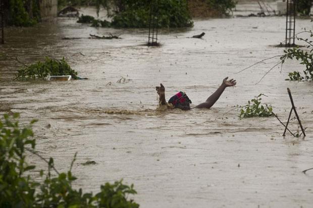 Mulher enfrenta área inundada em Porto Príncipe, no Haiti. (Foto: Reuters)