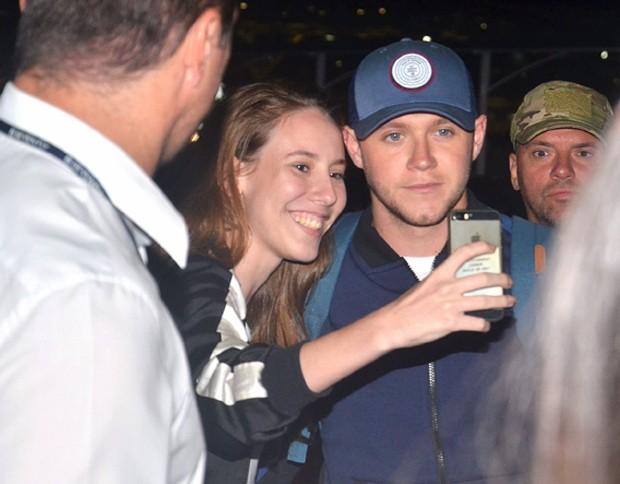 Niall posando com uma fã no aeropoto  (Foto: Webert Belicio / Ag News)