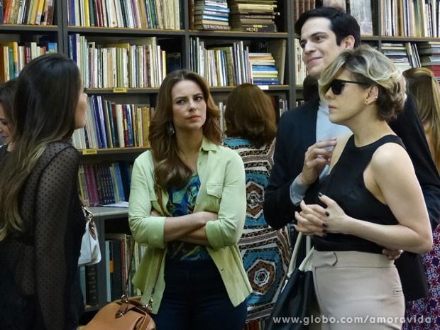 Paloma presta atenção na conversa e estranha (Foto: Amor à Vida/ TV Globo)