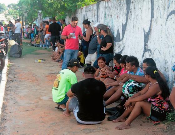 Parentes aguardam no IML de manaus (ao lado).Muitas souberam das mortes por vídeos de assassinatos nas redes sociais (Foto:  Arthur Castro/Em Tempo/Agência A Tarde/Folhapress)