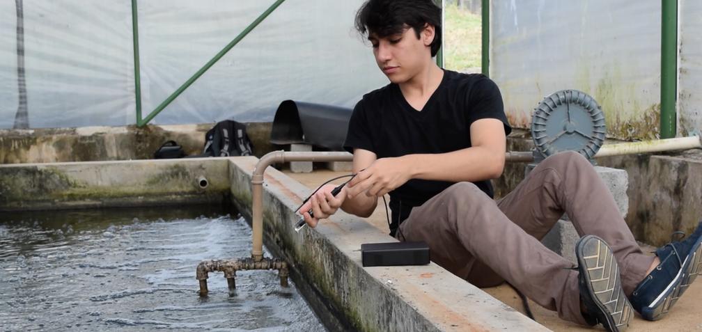 Elton Soares, integrante da equipe, instala dispositivo em tanque de produção de peixes (Foto: Carlos Eduardo Milani)
