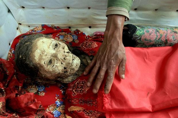 Corpo preservado de uma mulher é homenageado por familiares. (Foto: Elang Herdian/AP)