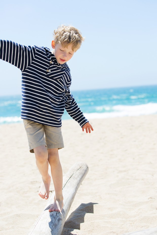 positive happy boy walking on the old trunk at the beach being active and playful at the beach (Foto: Getty Images/iStockphoto)