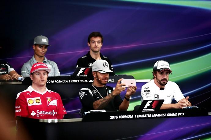 Lewis Hamilton mexe no celular durante coletiva de imprensa da Fórmula 1 no Japão (Foto: AFP)