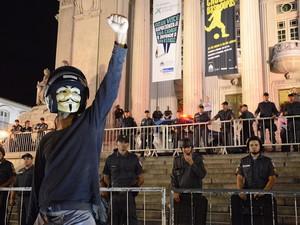 Manifestante mascarado comemora protesto em frente a grupo de PMs na Assembleia Legislativa do Estado do Rio de Janeiro (Alerj) (Foto: Bruno Jenz/Eleven/Estadão Conteúdo)