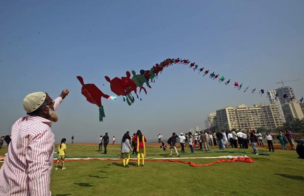Homem empina pipa extensa durante festival na Índia (Foto: Rafiq Maqbool/AP)