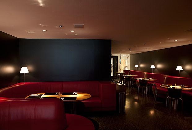 O mobiliário, desenhado pelo escritório Vainer Arquitetos, inclui assentos estofados de espuma com couro vermelho e mesas com tampo laminado de madeira muiracatiara e base de aço inox. Cadeiras Highframe da Scandinavia Designs  (Foto: Fernando Laszlo/Divulgação)