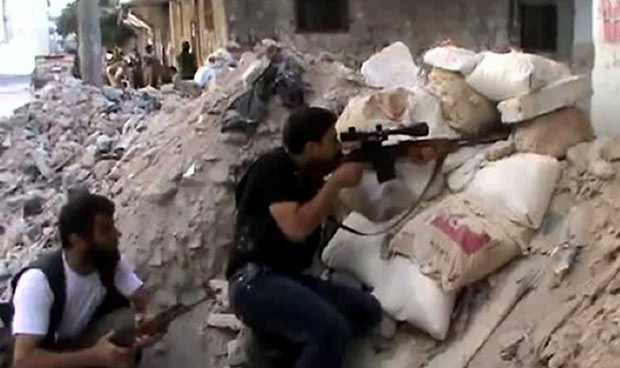 Imagem tirada de vídeo divulgado pela oposição mostra rebeldes combatendo no bairro de Salaheddin, na cidade de Aleppo (Foto: AFP)