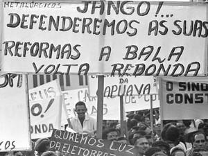 Centenas de pessoas carregando faixas e placas de protesto chegam ao comício na Central do Brasil, organizado pelo então presidente João Goulart (Foto: Domicio Pinheiro/Estadão Conteúdo)