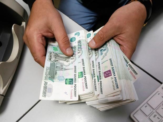 Funcionário conta notas de rublo em um escritório em Krasnoyarsk, na Sibéria (Foto: Ilya Naymushin/Reuters)