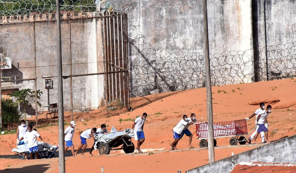 Detentos carregam os corpos de mortos após rebelião no presídio de Alcaçuz, no Rio Grande do Norte (Foto: Josemar Gonçalves/Reuters)