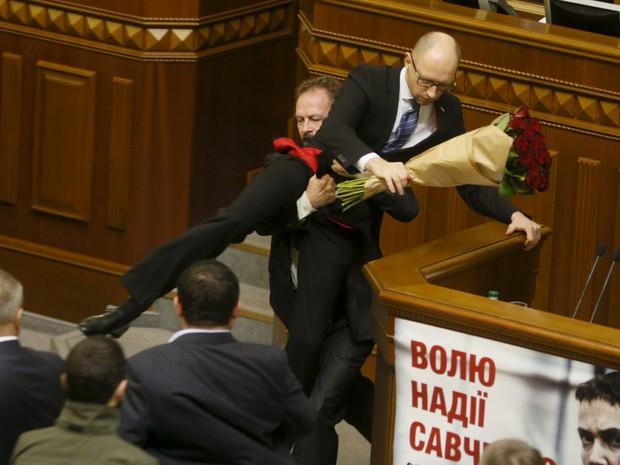O deputado Oleg Barna, do partido do presidente ucraniano, Petro Poroshenko, se aproximou da tribuna, entregou um buquê de rosas com uma fita preta a Yatseniuk - que nesse momento fazia um balanço da gestão de seu governo em 2015 - e em seguida o agarrou  (Foto: Valentyn Ogirenko/Reuters)