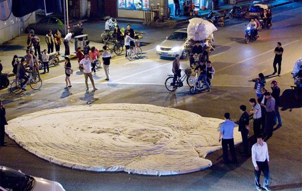 Pessoas observam curiosas a espuma branca e fedida que foi expelida depois que parte do asfalto se rachou em Nanjing, na província chinesa de Jiangsu. Os moradores suspeitam que a causa, ainda investigada, seriam as obras do metrô em construção ali perto. (Foto: AFP)