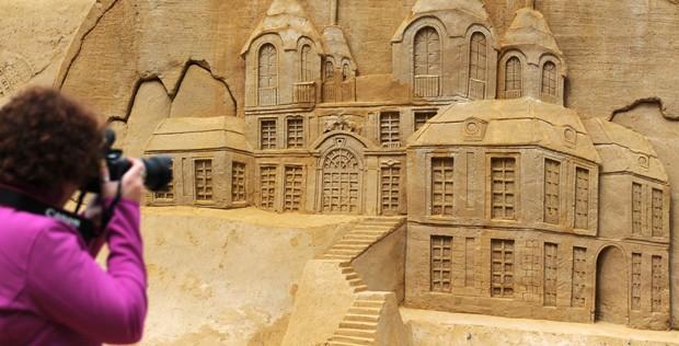 Visitante fotografa escultura 'Palácio Favorito', de Maxim Gazendam. Exposição reúne 16 obras feitas com areia (Foto: Daniel Bockwoldt/AFP)