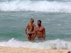 Namorada de Henri Castelli dá ajeitadinha no biquíni em praia do Rio